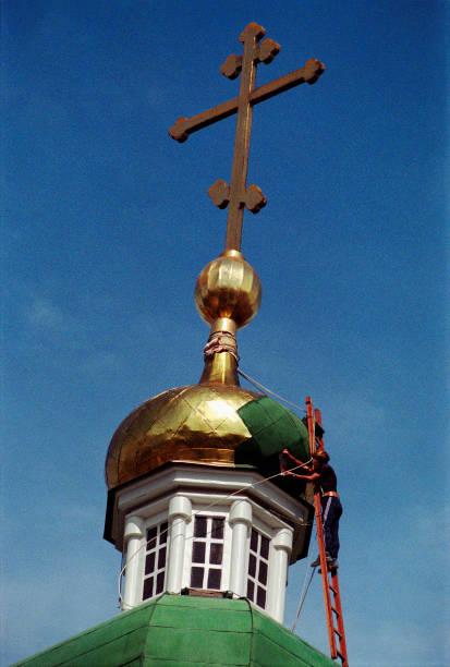 der arbeitnehmer erstreckt sich die kuppel mit goldfolie. belfried von astrachan kreml, russland - typisch 90er stock-fotos und bilder