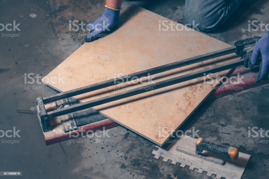 The worker cuts a square tiles of large size with a hand tile
