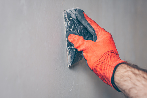 The worker grinds the wall with sandpaper