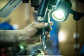 The worker is working with vertical metal milling machine