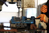 The worker is working with vertical metal milling machine to hole to steel material in the workshop.