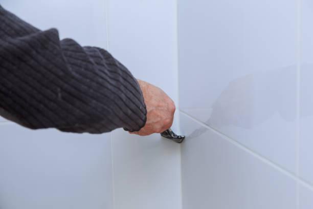 der arbeiter repariert den fliesenleger an der wand mit dem schornstein, entfernt weißes silikon aus verlegekacheln und veredelung. - fugen reinigen stock-fotos und bilder