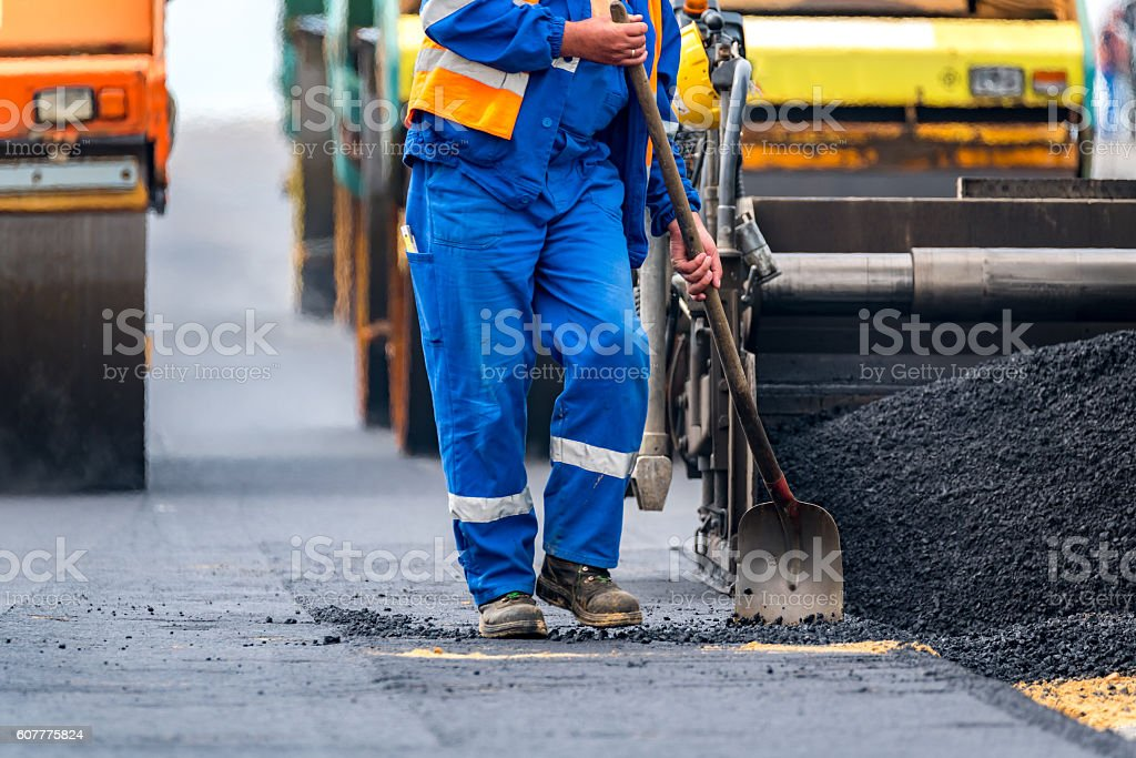The workers and the asphalting machines stock photo