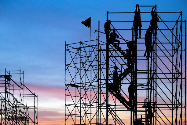 The workers are climbing the silhouette of scaffolding in the high altitude, horizontal and vertical scaffolding formed a myriad of grid, industrial and modern urban construction background The workers are climbing the silhouette of scaffolding in the high altitude, horizontal and vertical scaffolding formed a myriad of grid, industrial and modern urban construction background scaffolding stock pictures, royalty-free photos & images