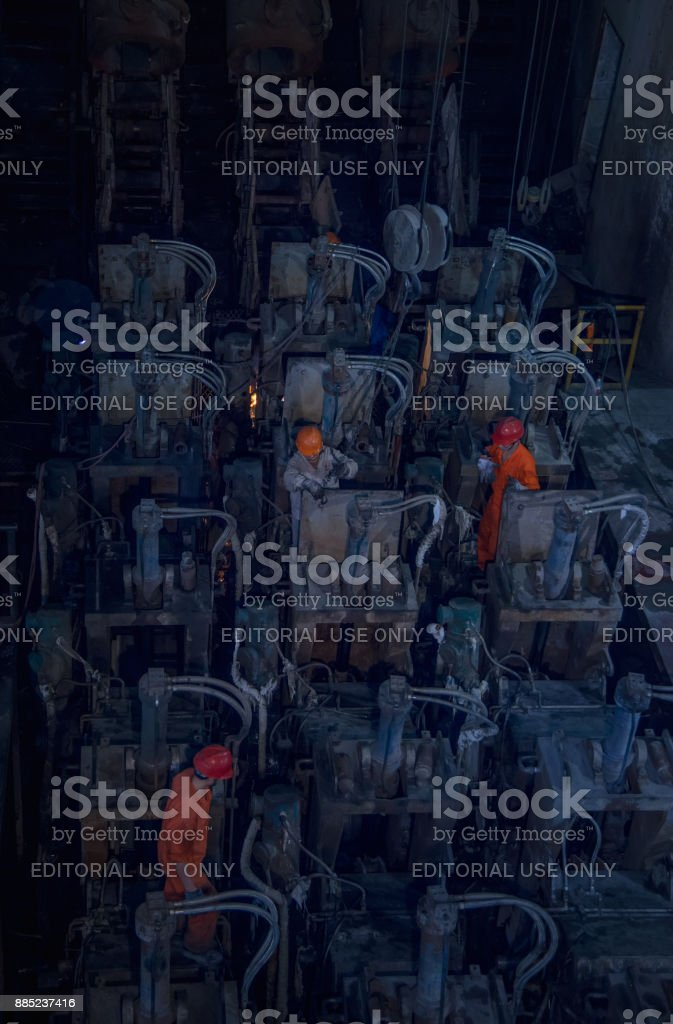 The workers are overhauling the electrodes in the steel plant stock photo