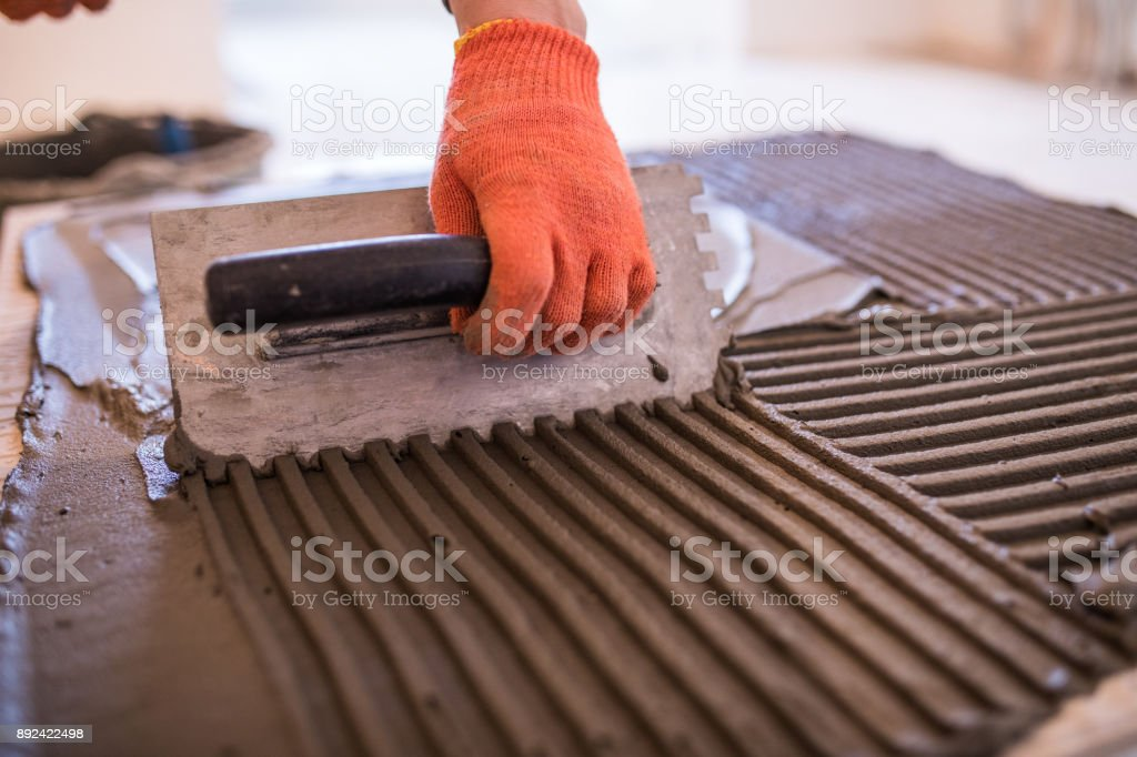 The worker's hand is putting tiles adhesive to the wall with the notched trowel. Laying Ceramic Tiles. stock photo
