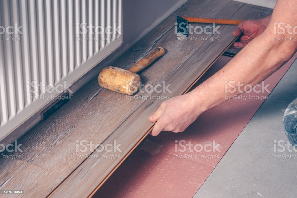The worker's hand with a hammer mounts the floorboard into place royalty-free stock photo