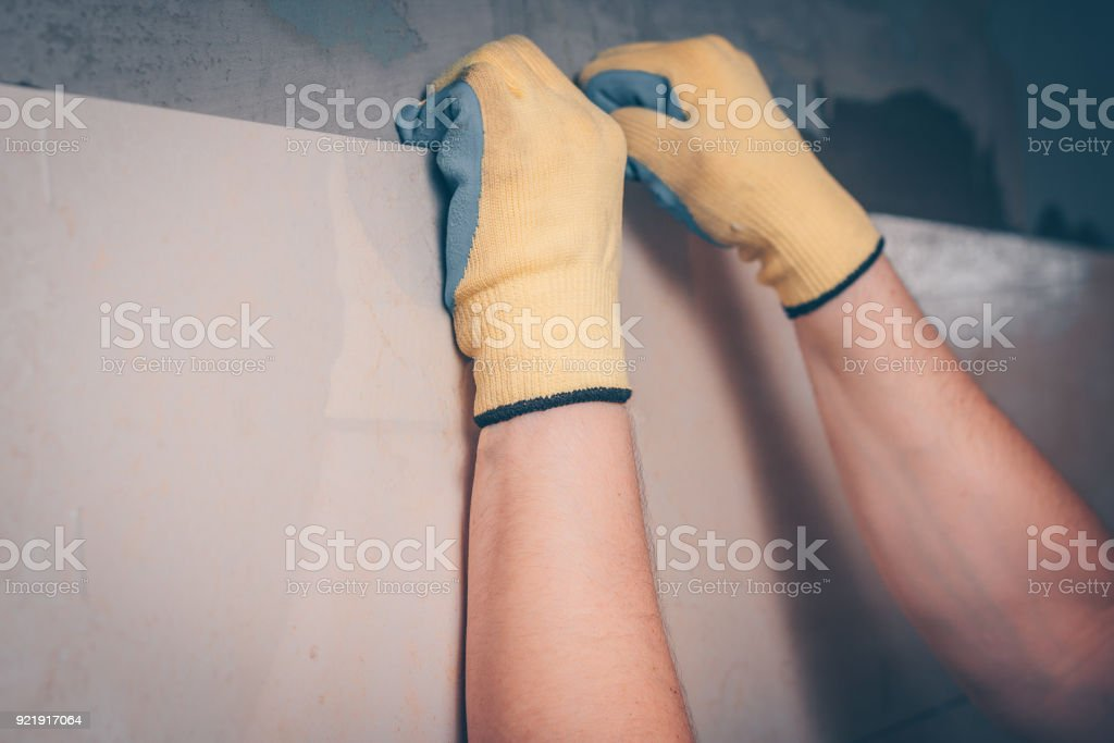 The working tiler puts the tiles on the wall, adjusts the position of...