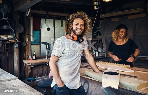 Portrait of two happy young men working on skateboards in their workshop