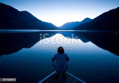 Person sitting quietly on the edge of a dock watching the sunset