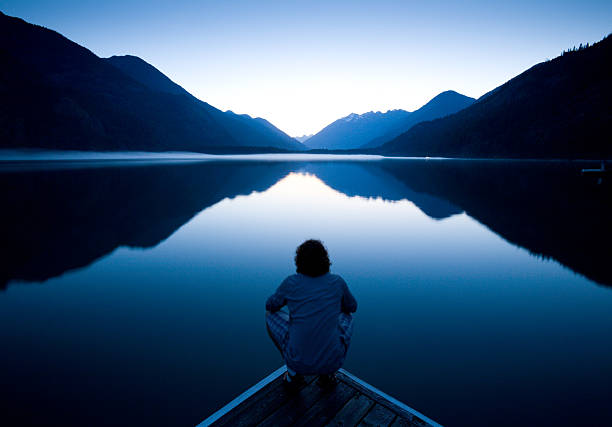 The World at Rest Person sitting quietly on the edge of a dock watching the sunset tranquil scene stock pictures, royalty-free photos & images