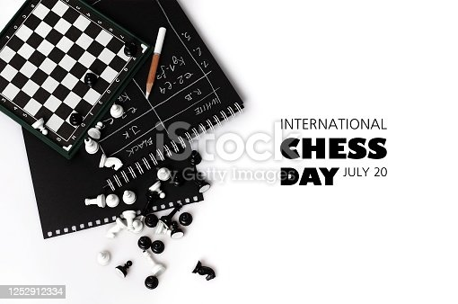 The world day of chess. International chess day. July 20. Holiday greeting poster. Small chess pieces and a chessboard are scattered on the table. White isolated background. Text. Copy space.