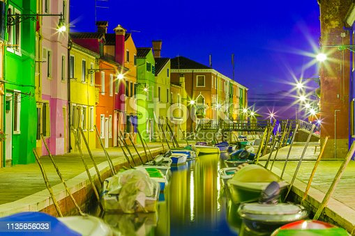 Boats lining one of the many small side canals at night on the island of Burano off Venice