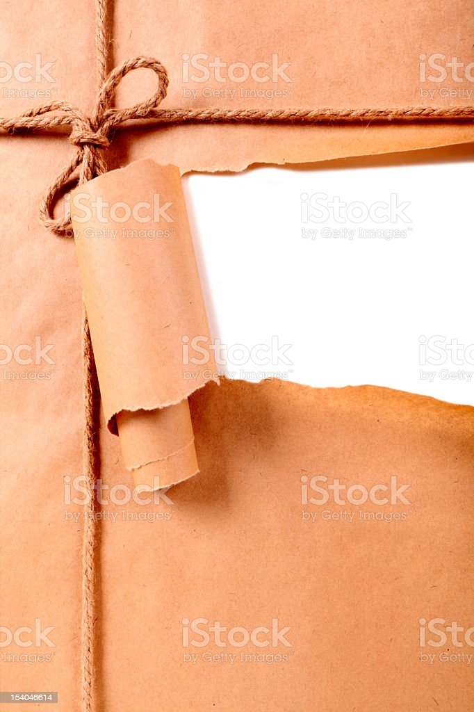 The wrapping paper ripped open on a tied up brown parcel stock photo