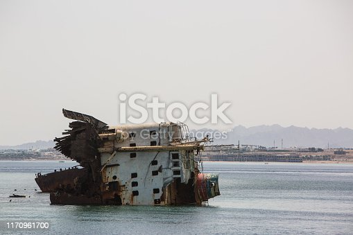 View of a old sunken rusty ruined ship on a shoal in sea Old seagoing vessel. The ship crashed on a reef. Stranded. Sticks out of the water. Diving spot. Red Sea, Egypt. Tiran Island.
