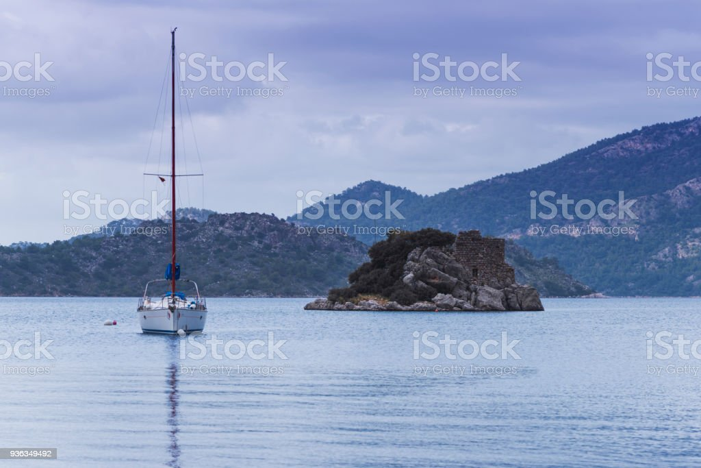 The yacht moored next to the island with the ruins of a small castle stock photo