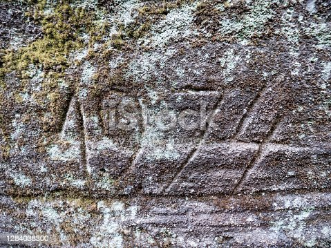 The year 1974 engraved into the sandstone rock. Someone  engraved modern numbers rocky wall in sandstone quarry.