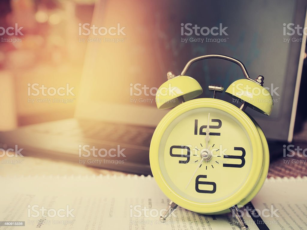 The yellow alarm clock is showing 12 o'clock. stock photo
