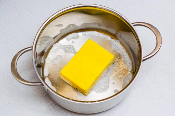 Sarı bulaşık süngeri sabunlu tavanın dibinde yatıyor. stok fotoğrafı