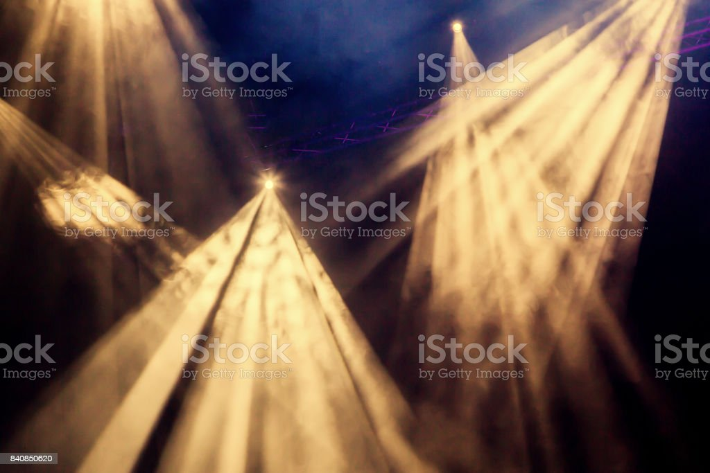 The yellow light rays from the spotlight through the smoke at the theater or concert hall. Lighting equipment for a performance or show stock photo