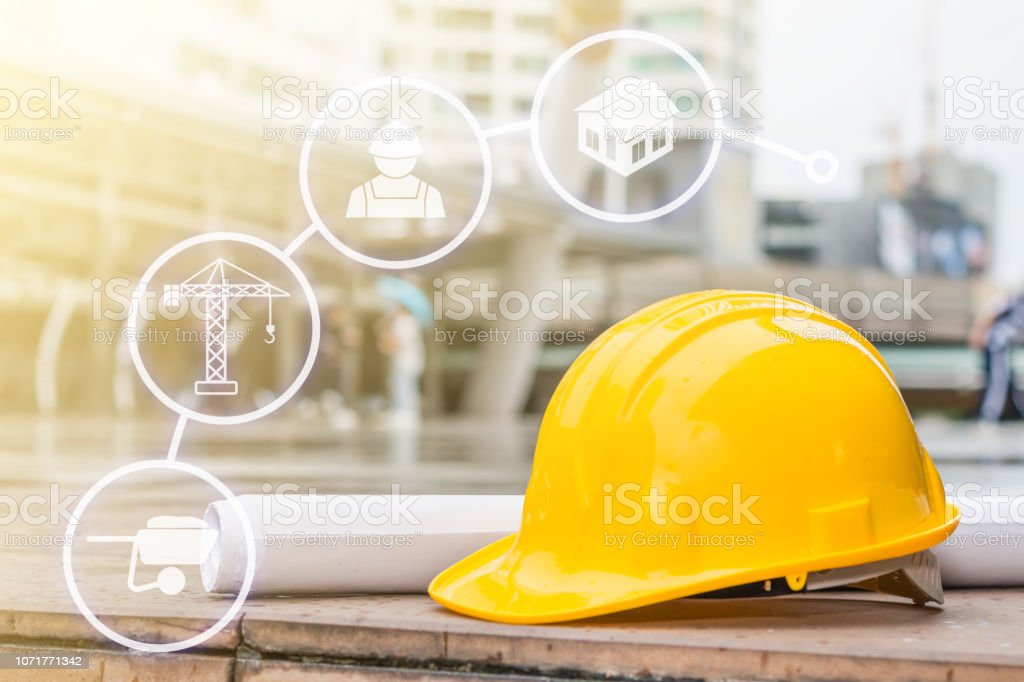 The yellow safety helmet put on the blueprint at construction site with construction icon technology stock photo