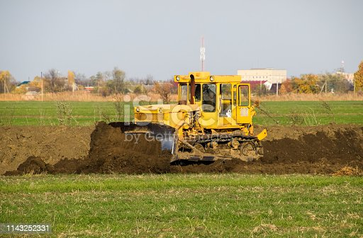 The yellow tractor with attached grederom makes ground leveling. Work on the drainage system in the field.
