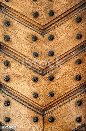 The yellow wood texture with diagonal lines and metal bolts. The vertical frame.