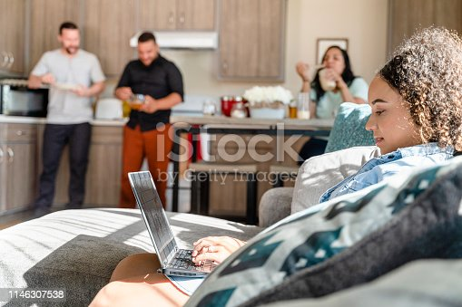 istock The young African-American woman working with a PC laptop in the living room of a shared apartment, when her roommates preparing food, eating and talking in the backdrop. 1146307538