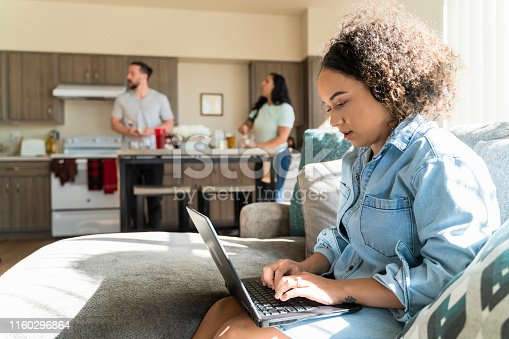 istock The young African-American woman working with a PC laptop in the living room of a shared apartment, when her roommates preparing food, eating and talking in the backdrop. 1160296864