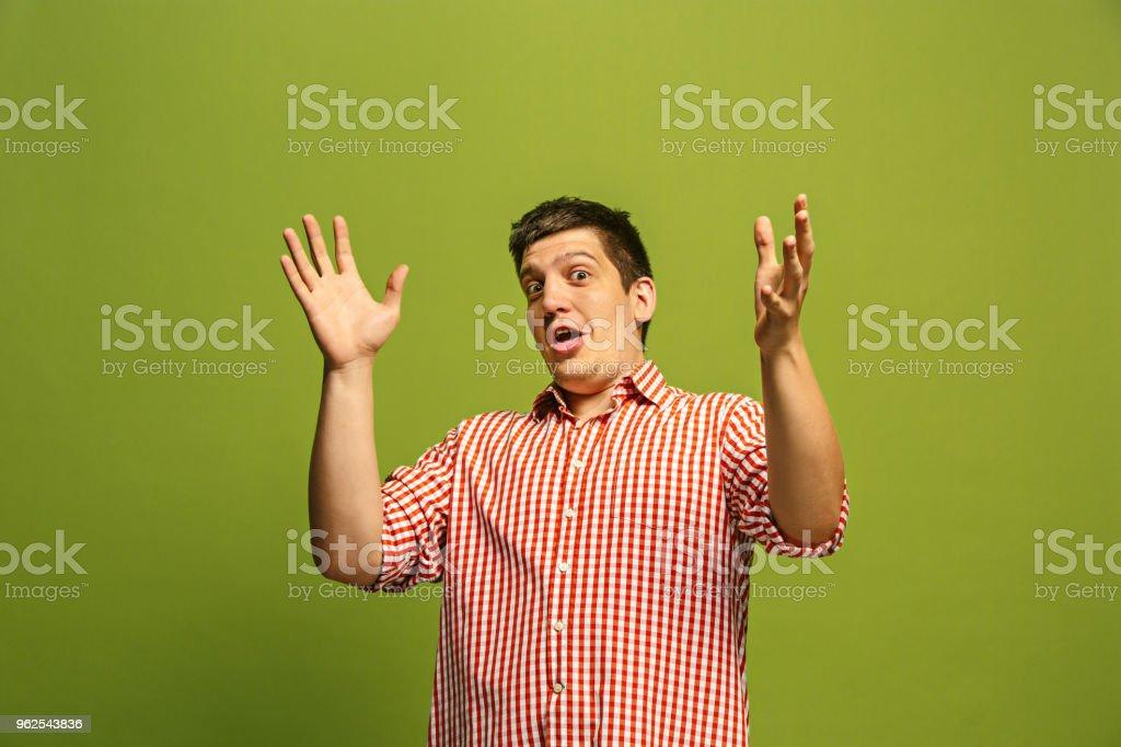 O jovem homem atraente olhar surpreso isolada em verde - Foto de stock de Adulto royalty-free