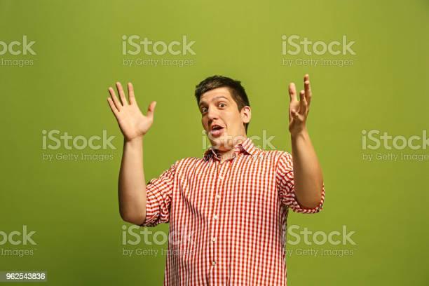 Foto de O Jovem Homem Atraente Olhar Surpreso Isolada Em Verde e mais fotos de stock de Adulto