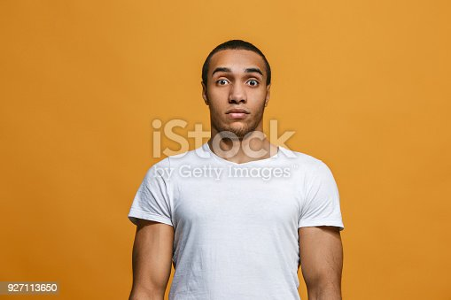 1012628232istockphoto The young attractive man looking suprised isolated on orange 927113650