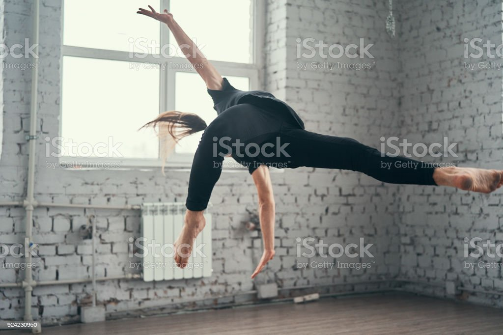 The young attractive modern ballet dancer in black jacket stock photo