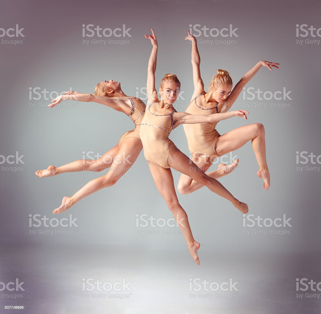 The young beautiful ballerina dancer jumping on a gray background stock photo