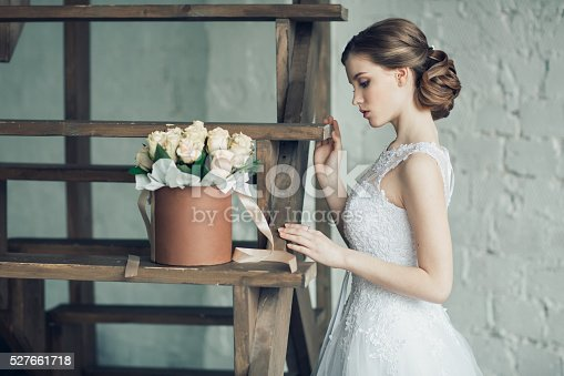 istock The young beautiful bride with roses in the box 527661718