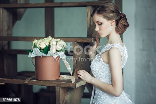 istock The young beautiful bride with roses in the box 527661978