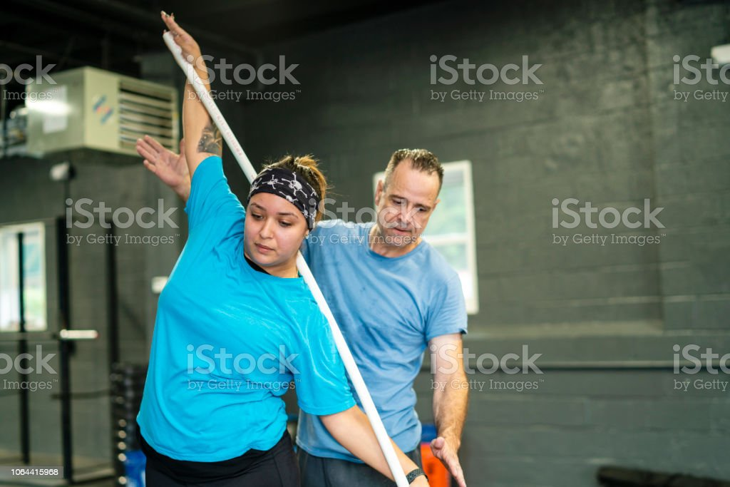 The young, beautiful cheerful body-positive Latino woman doing stretching exercise with a pole under the supervision of the Senior Latinx man, the coach, in the gym stock photo