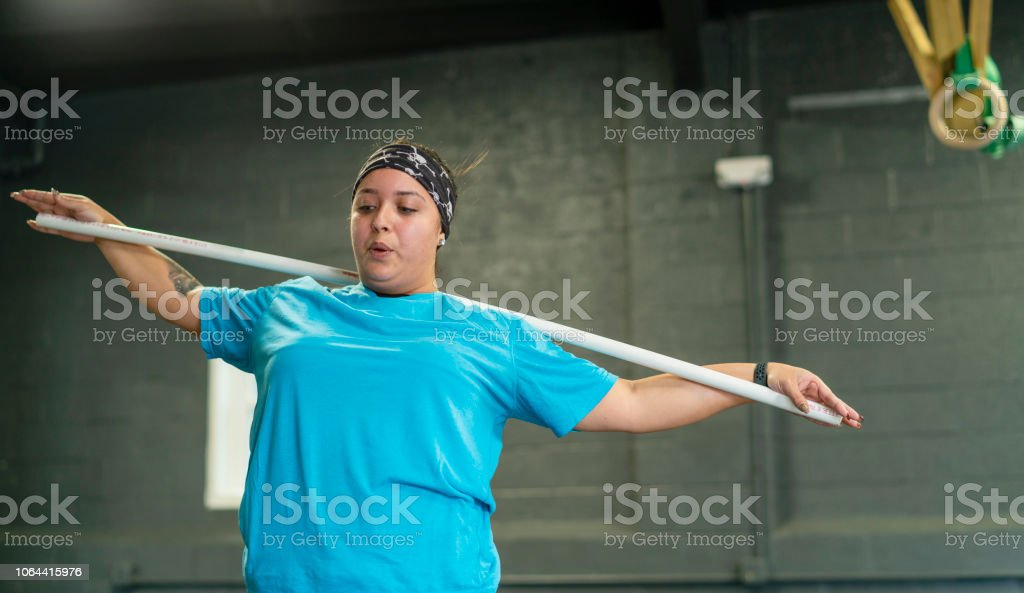 The young, beautiful cheerful body-positive Latino woman doing stretching exercise with a pole in the gym stock photo