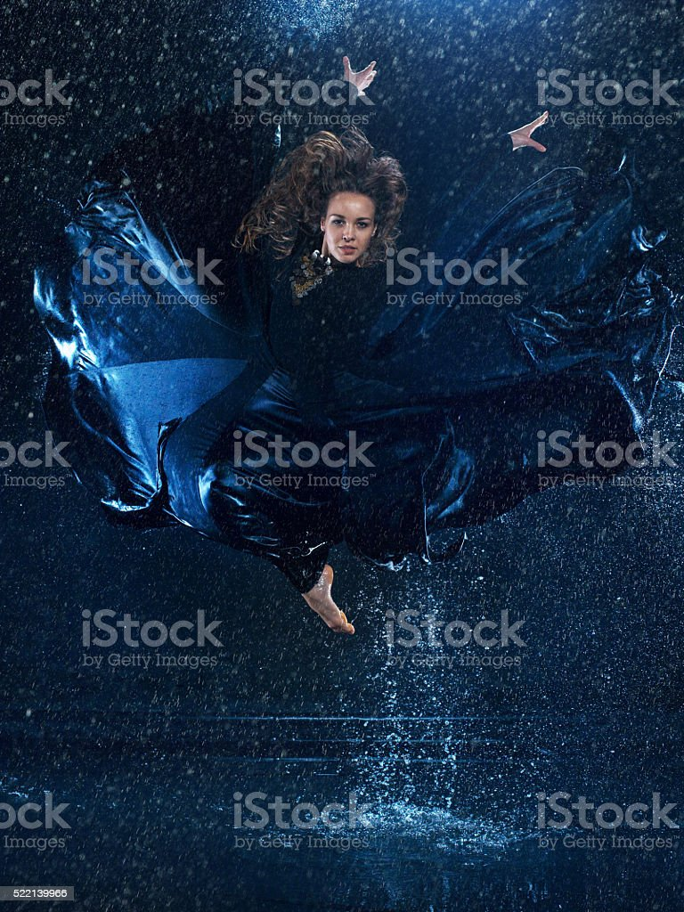 The young beautiful modern dancer dancing under water drops stock photo