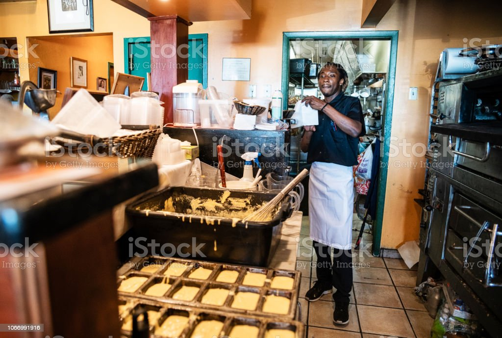 The young Black man, bartender and waiter, working in the small local restaurant stock photo
