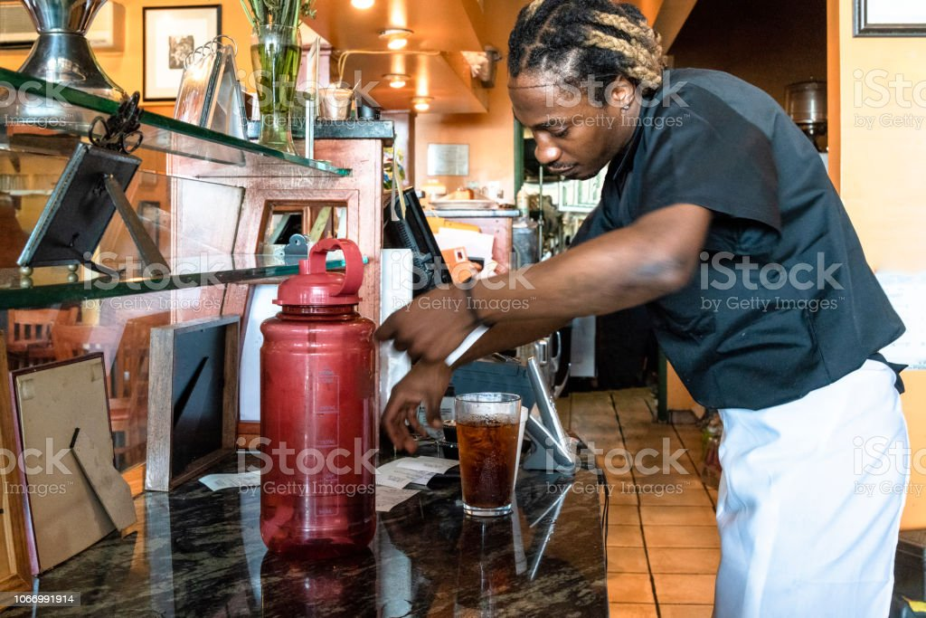 The young Black man working with the cash register behind the counter of the small local restaurant stock photo