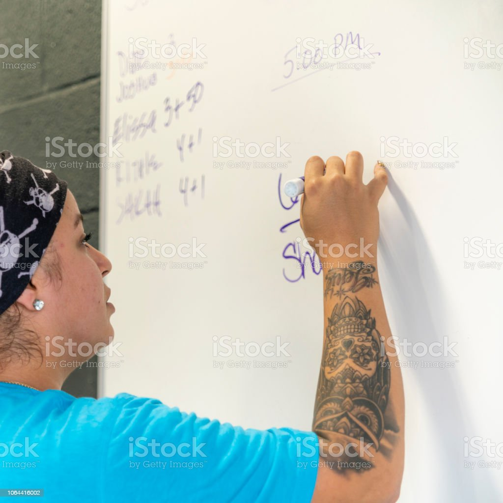 The young body-positive Latino woman writing notes on the whiteboard in the gym stock photo