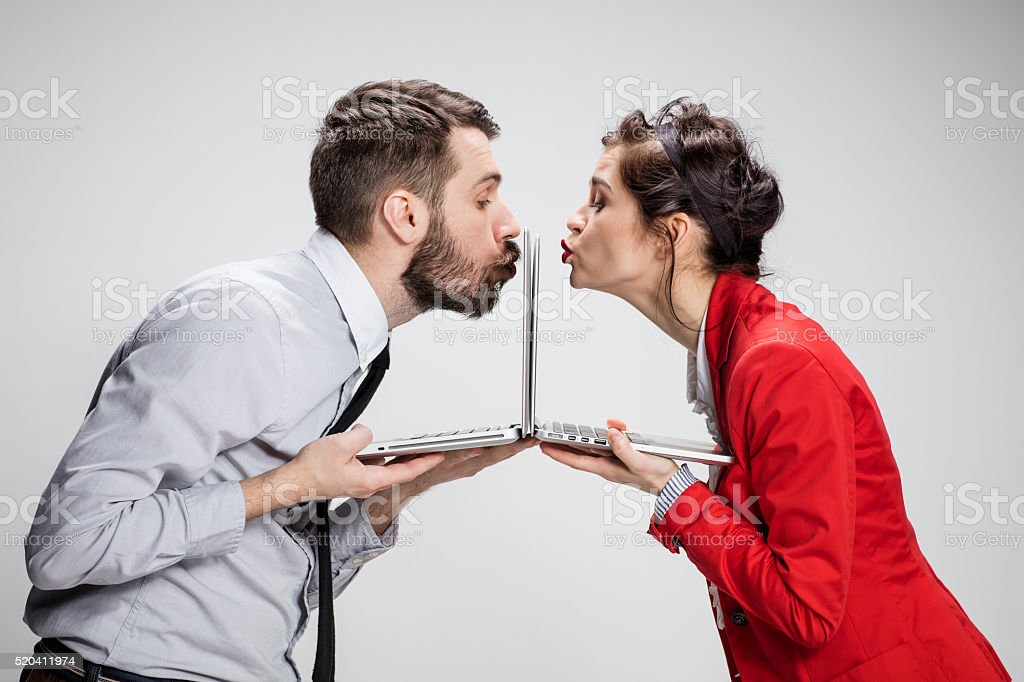 The young businessman and businesswoman with laptops kissing screens on stock photo