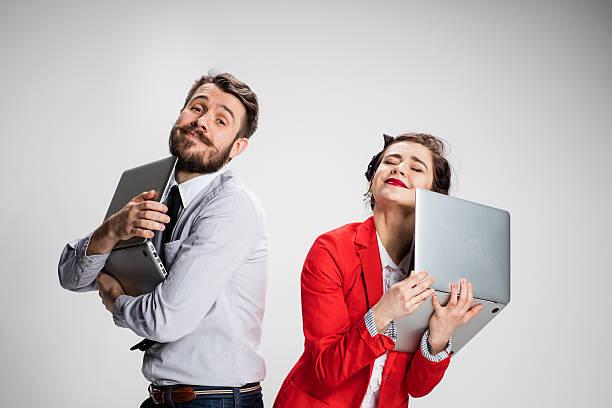 Le jeune homme d'affaires et femme d'affaires avec ordinateur portable sur fond gris - Photo