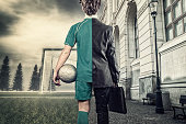 Young man half soccer player half bussiness man. In a city and  soccer field.