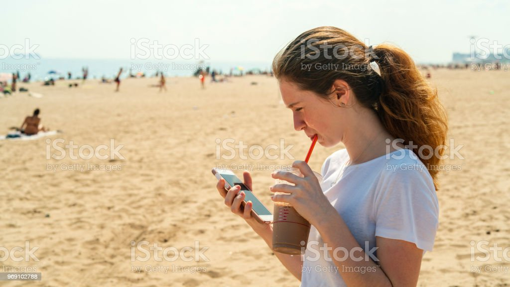 The young cheerful 18-years-old girl chatting with a smartphone and drinking a milkshake at Brighton Beach – zdjęcie