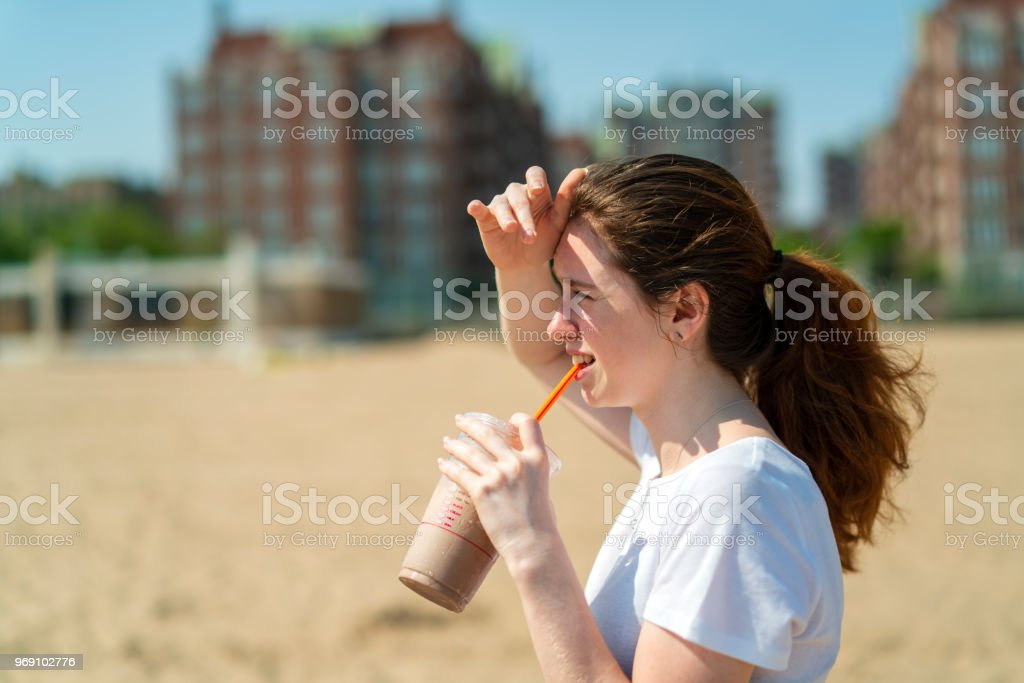 The young cheerful 18-years-old girl drinking a milkshake on Brighton Beach – zdjęcie