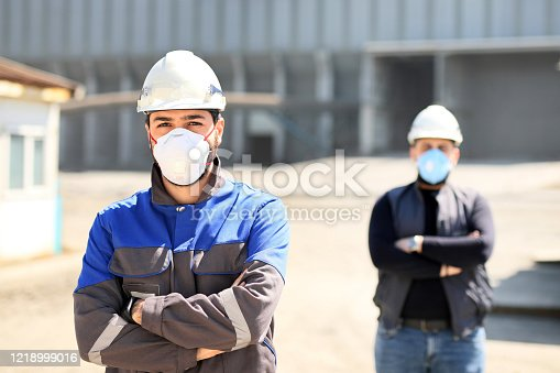 The young civil engineers are working with protective mask in the construction field.