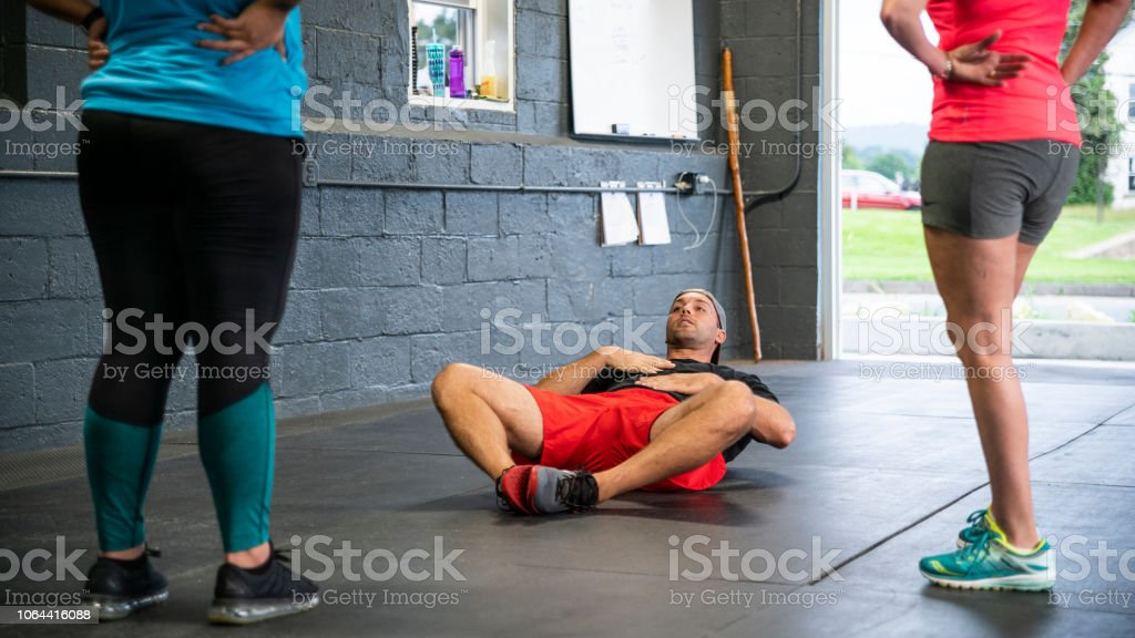 The young coach showing how to properly execute exercise to the group of the Latino women stock photo