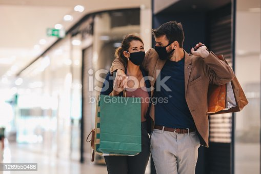 The young couple carries shopping bags and walks through the mall, wearing protective masks, life in a time of pandemic